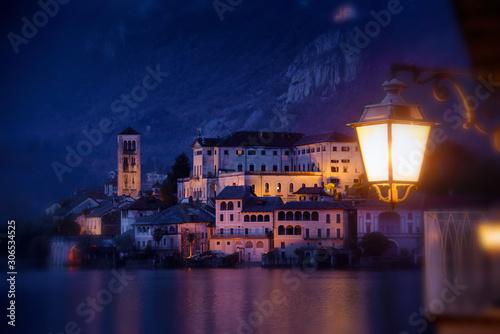 Obraz Isola di Orta San Giulio di notte al tramonto con illuminazione cittadina e  lampione acceso - fototapety do salonu