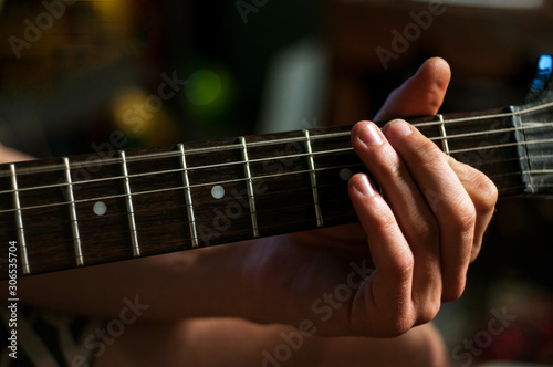 Photo  Close up guitarist tune up guitar strains.