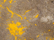 A Rough Textured Concrete Surface With Patched Of Yellow Flaking Paint