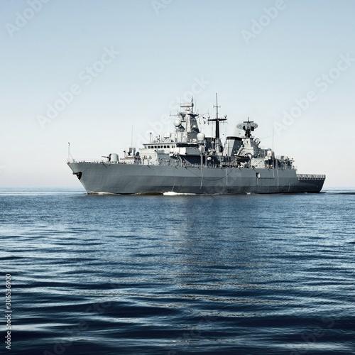 Photo Grey modern warship sailing in still water