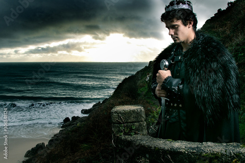 Photo Handsome king with goatee stands on stone balcony with sword and crown, praying