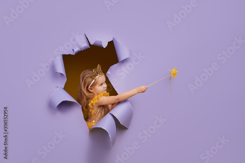 Fotografie, Tablou Cute little child girl in princess costume breaks through a colored purple paper wall