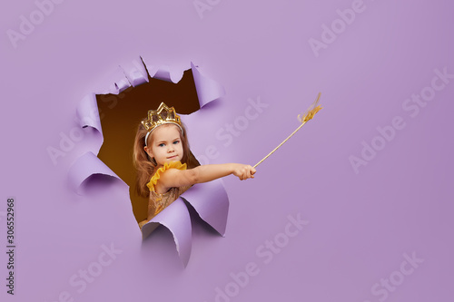 Cute little child girl in princess costume breaks through a colored purple paper wall. Points with a magic wand to the empty space on the right. Toddler funny emotions face.