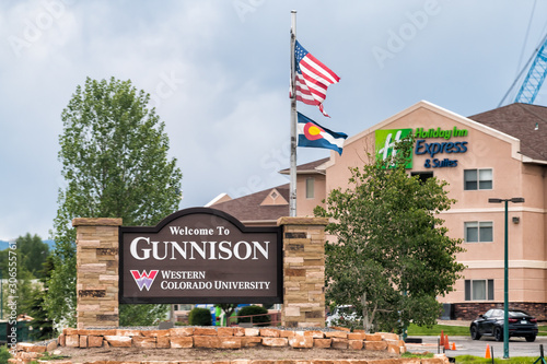 Gunnison, USA - June 20, 2019: Highway 50 in Colorado with sign for city entrance welcome and university with american flag