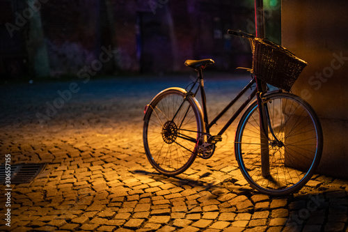 Papiers peints Velo a bicycle lashed to a pole on a city street, lit by a lamp at night