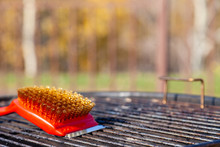 Close-up Of A Red Brush With Golden Bristles And A Scraper For Cleaning A Barbecue Grill Grate. The Concept Of Cleaning After Lunch In Open Air, Picnic, Barbecue, Lunch