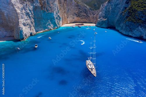 Aerial drone shot of luxury yacht leaving Zakynthos shipwreck navagio beach in s Fototapeta
