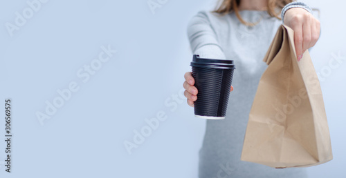 Fototapeta Woman holding cardboard cup of coffee and package food take and go in hand on gr