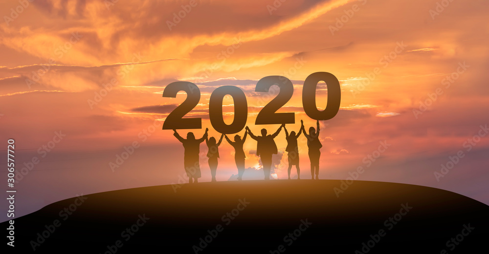 Fototapeta Happy new year 2020, Silhouette of 2020 letters on the mountain with business people raised arms in teamwork concept at sunrise.