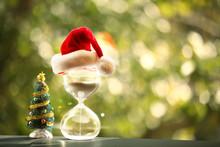 Christmas Countdown. Modern Hourglass And Christmas Tree -- Sand Trickling Through The Bulbs Of A Crystal Sand Glass. Holiday-themed Image.