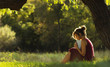 sunny portrait of a beautiful girl sitting on green glade under tree branches with book, woman reading novel on nature, concept hobby and lifestyle