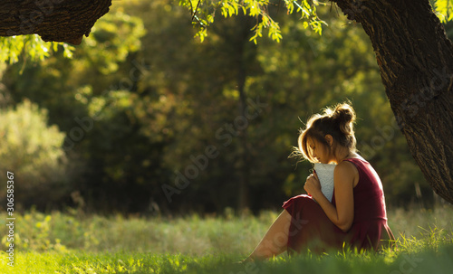 Valokuvatapetti sunny portrait of a beautiful girl sitting on green glade under tree branches wi