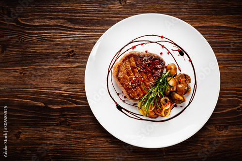 Fototapeta Grilled sirloin steak and vegetables on wooden background