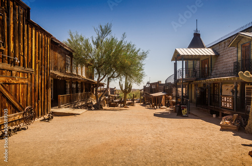 Fototapeta Old Western Goldfield Ghost Town square with huge cactus and saloon, photo taken during the sunny day with clear blue sky obraz