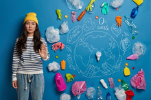 No Plastic And Environmental Pollution. Serious Asian Woman Pulls Palm Forward, Wears Yellow Hat, Striped Jumper And Denim Pants, Asks Not To Pollute Our Planet, Makes Symbolic Picture On Blue Wall