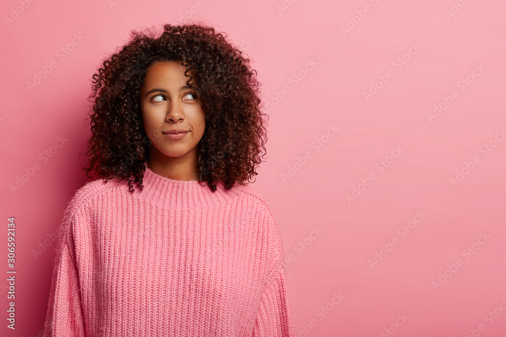 Fototapety, obrazy: Half length shot of pretty thoughtful woman with Afro hairstyle looks pensively aside, thinks deeply about something, thinks how to act in difficult situation, wears pink knitted sweater stands indoor