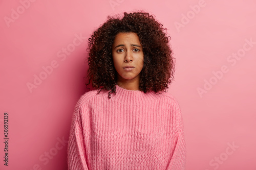 Obraz Photo of upset Afro woman has regretful look, displeased face expression, dressed in casual clothes, unhappy with bad news, looks sadly at camera, wears sweater, isolated on pink background. - fototapety do salonu