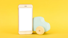 Mobile Phone And Children's Blue Toy Car On A Yellow Background