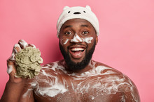 Funny Black Bearded Man Washes His Torso, Has Foam On Body And Face, Laughs Happily, Holds Sponge, Wears Bath Hat, Isolated On Pink Background. Naked Macho Takes Shower Or Douche. Hygiene Concept