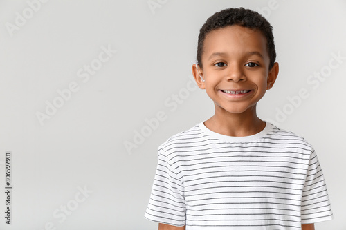 Photo Little African-American boy with hearing aid on light background