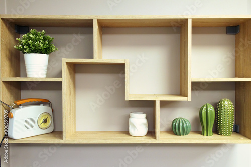Fotografía Home interior decoration, wooden wall shelf with objects composition- vase, decorative elements from ceramic, pot with plant, retro style radio