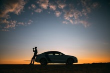 Silhouette Of Man Driver Relaxing After A Ride, Standing Next To His Car And Drinking Water From A Bottle, Side View. Sunset Time.