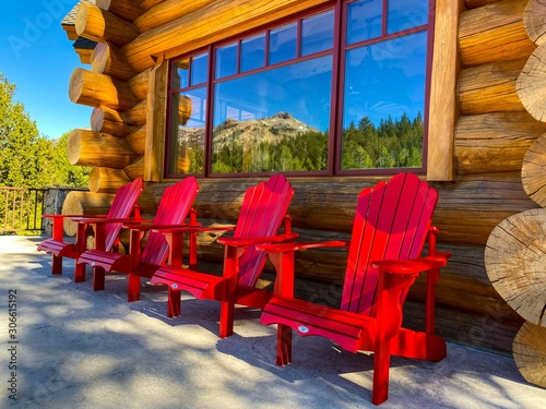 Red Adirondack Chairs on Log Cabin Deck Canvas Print