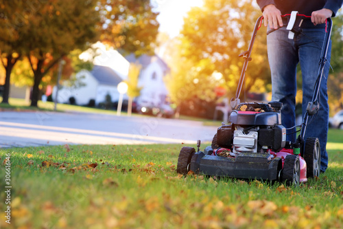 Fotografia Mowing the grass with a lawn mower in sunny autumn