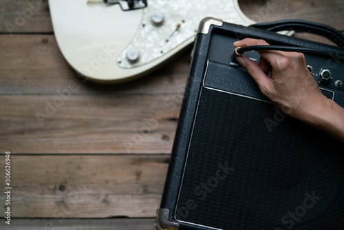 Fotografija Guitar amplifier and woman hand plugging cable into the amplifier guitar, on woo