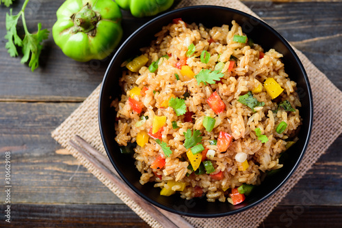 Fried rice with vegetables in a black bowl, Asian food, top view Fototapeta