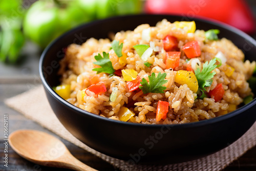 Fotografia Fried rice with vegetables in a black bowl, Asian food
