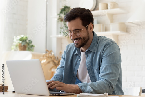 Fototapeta Smiling young man using laptop studying working online at home obraz