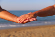 Hands of man and woman against the background of the sea. The joined hands of man and woman. The concept of love and family.