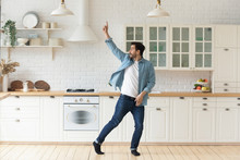 Carefree Funny Young Man Having Fun Dancing Alone In Kitchen