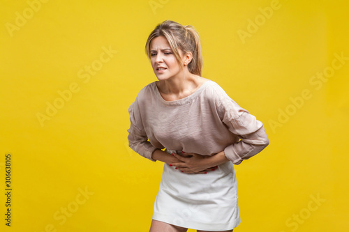 Portrait of unhealthy young woman with fair hair in casual beige blouse standing, touching stomach with arms, suffering pain, gastritis or indigestion Wallpaper Mural
