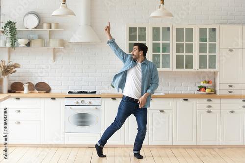 Cuadros en Lienzo Carefree funny young man having fun dancing alone in kitchen