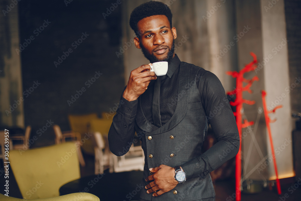 Fototapeta A young and handsome dark-skinned boy in a black suit standing in a cafe