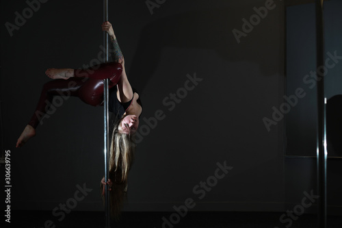 The dancer on the pylon in the studio. Girl doing exercises on a sports equipment. - 306639795