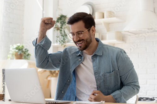 Photo Excited young man looking at laptop celebrating online victory
