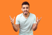 How Could You? Portrait Of Annoyed Frustrated Brunette Man With Beard In White T-shirt Standing With Raised Hands And Indignant Face Asking Why. Indoor Studio Shot Isolated On Orange Background