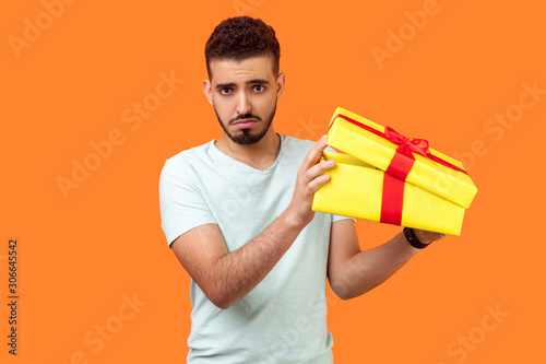 Vászonkép Portrait of dissatisfied brunette man with beard in white t-shirt unpacking holiday present and looking upset disappointed at camera, opening bad gift