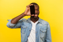 Portrait Of Happy Cheerful Man In Denim Casual Shirt Covering Half Face With Cellphone And Looking At Camera With Toothy Smile, Positive Glad Face. Indoor Studio Shot Isolated On Yellow Background