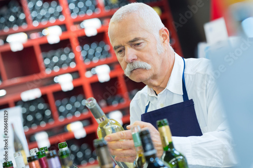 Photo  smiling senior man choosing wine at the supermarket