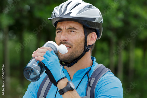 obraz PCV close view of male cyclist drinking water