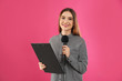 canvas print picture - Young female journalist with microphone and clipboard on pink background