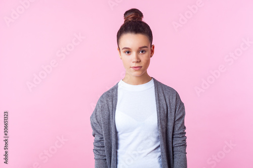 Fototapeta  Portrait of cute brunette teenage girl with bun hairstyle in casual pullover and T-shirt looking with serious expression, clean fresh face skin, natural beauty