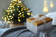 Christmas gift box on bed in festive interior