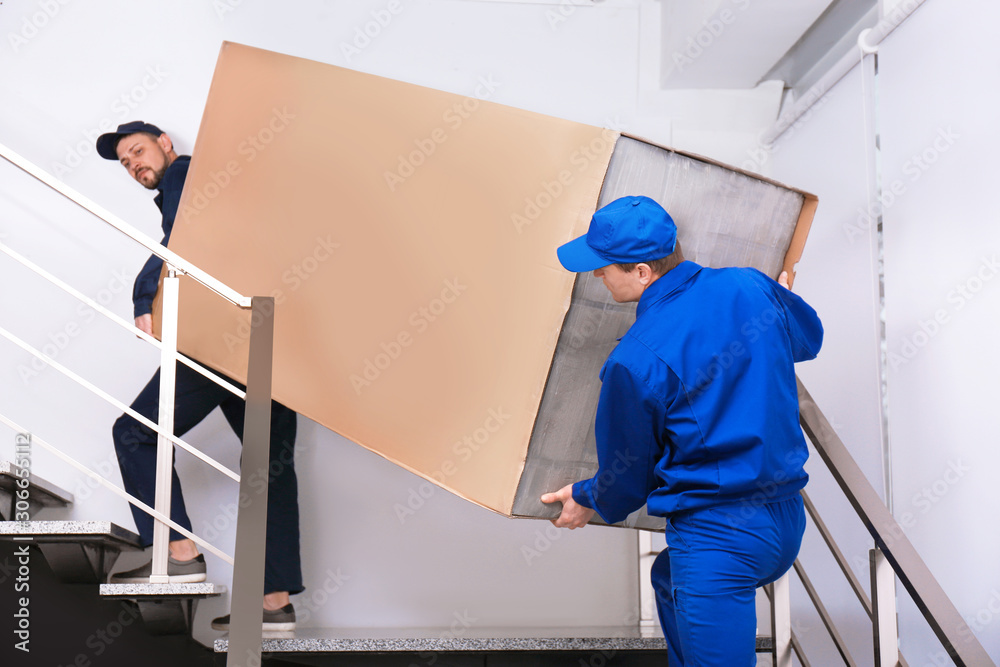 Fototapeta Professional workers carrying refrigerator on stairs indoors