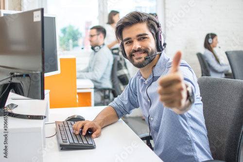 Cuadros en Lienzo  Smiling call center operator in headset looking at camera and showing thumb up