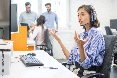Photo Confused young call center worker shrugging shoulders and looking at computer sc